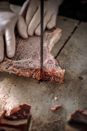 male butchers hand slicing meat
