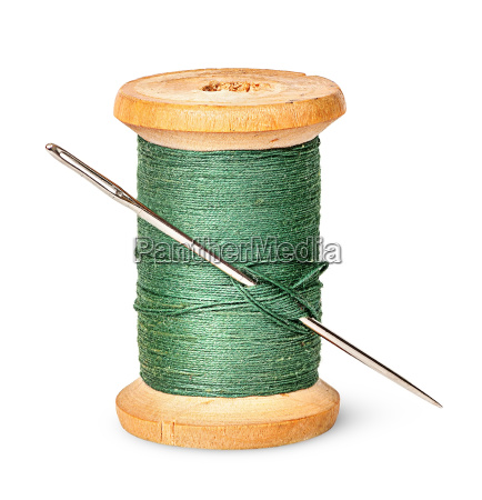 needle and thread on wooden spool