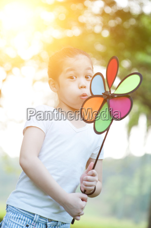 asian child blowing windmill outdoors
