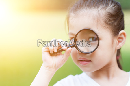 asian child with magnifier glass at