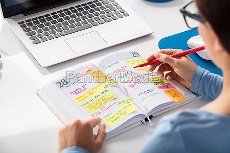 businesswoman marking schedule using planner