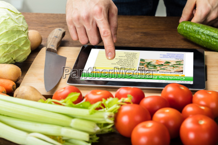 person is preparing recipe using digital
