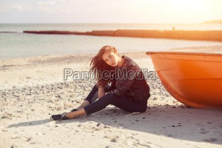 a girl sideways near a red