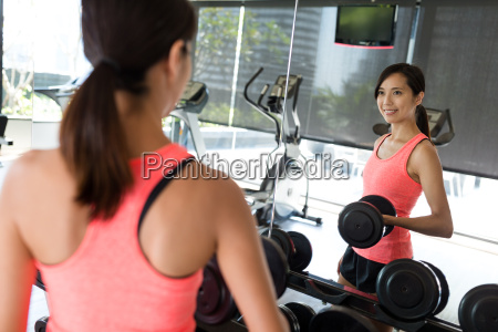 woman lifting up dumbbell in gym
