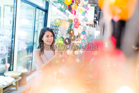 young woman choosing lantern in street