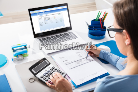 businesswoman calculating invoice using calculator