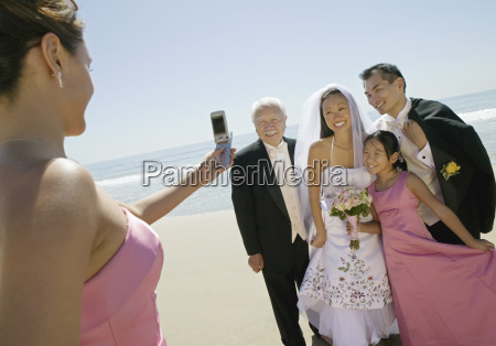 bridesmaid photographing newly weds with family
