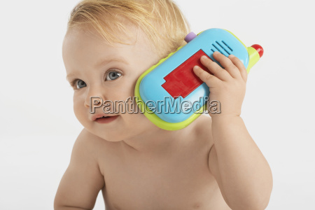 curious little boy using toy phone