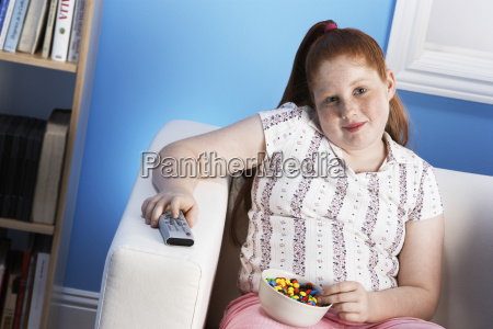 overweight girl with remote control eats