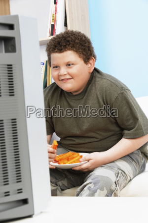 overweight boy with carrot sticks in