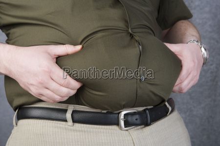 obese man grabbing his fat on