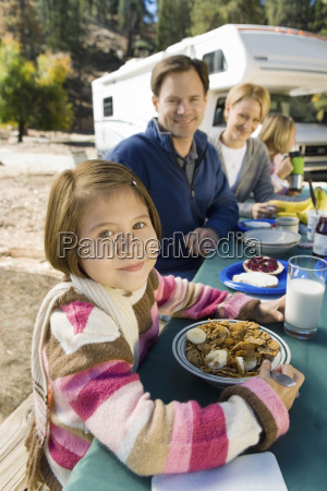 girl eating at picnic table with