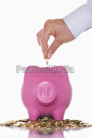 hand putting money in overflowing piggy