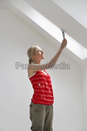 woman painting ceiling slope