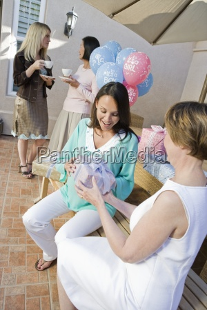 pregnant woman receiving baby shower gift