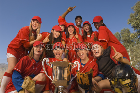 softball team and coach with trophy