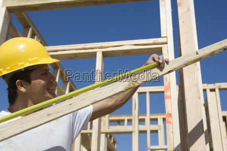 worker measuring lumber with measure tape