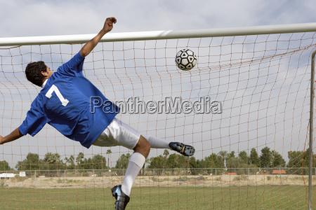 man scoring goal during soccer match