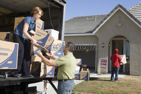 couple unloading moving boxes into new