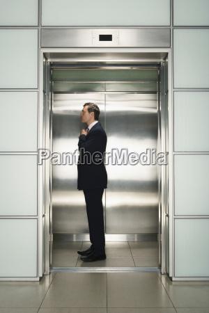 businessman adjusting necktie in elevator