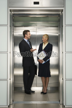 businesspeople communicating in elevator