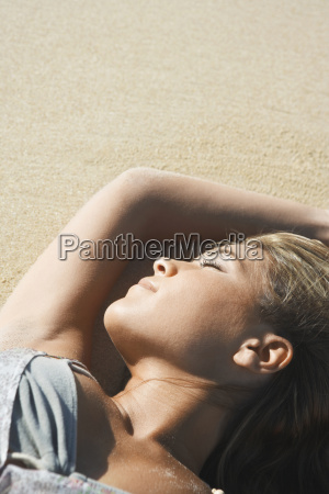 peaceful woman sunbathing on beach