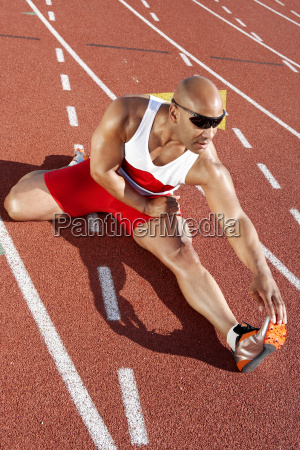 male athlete stretching on racetrack