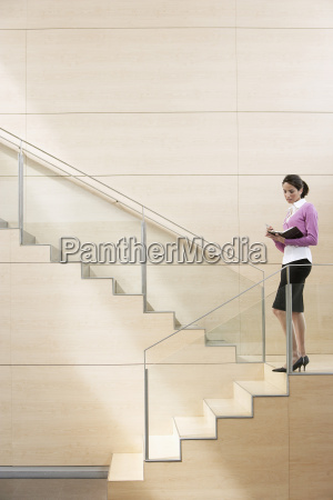 businesswoman writing in diary on steps