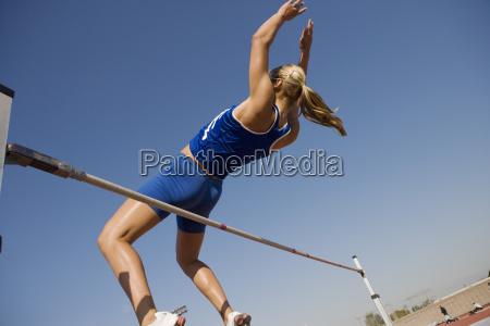 high jumper in midair over bar