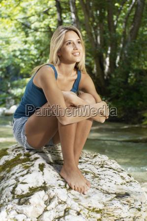 woman hugging knees while looking away