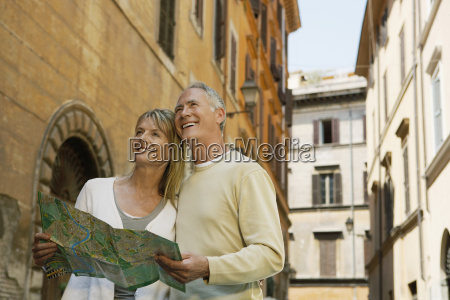 couple holding map on street in