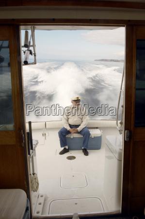 senior sailor sitting on yacht