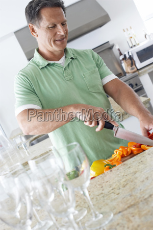 man chopping peppers at kitchen counter