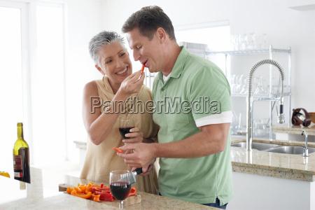 woman feeding pepper to man in