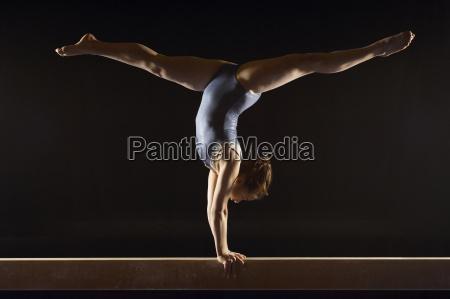 gymnast doing split handstand on balance