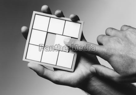 hands holding slide puzzle bw close