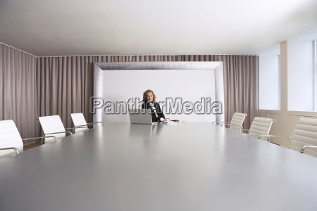 businesswoman sitting in boardroom with laptop