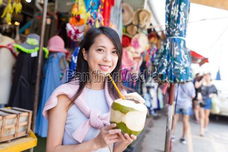 young woman enjoy coconut juciy in