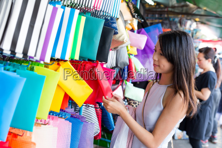 woman choosing clutch in street market