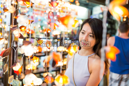 woman choosing lantern in street market