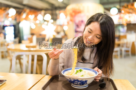 woman enjoy her noodles in japanese