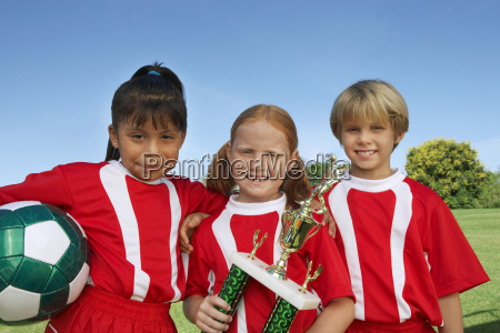 children with soccer ball and trophy