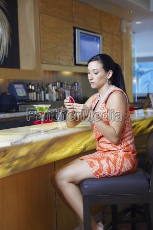woman text messaging at a bar