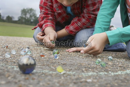 siblings playing marbles on playground