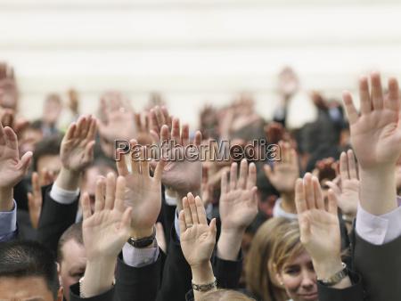 business crowd raising hands