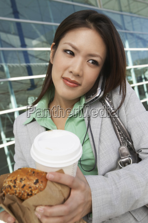 business woman on call holding takeout