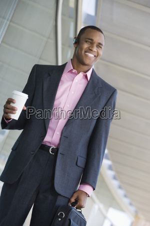 businessman holding takeout coffee and briefcase