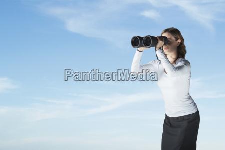businesswoman looking through large binoculars
