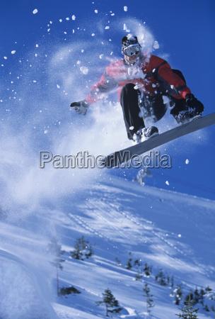 snowboarder in midair with snow powder