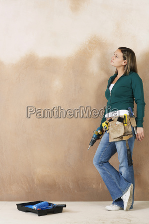 woman with toolbelt and drill leaning